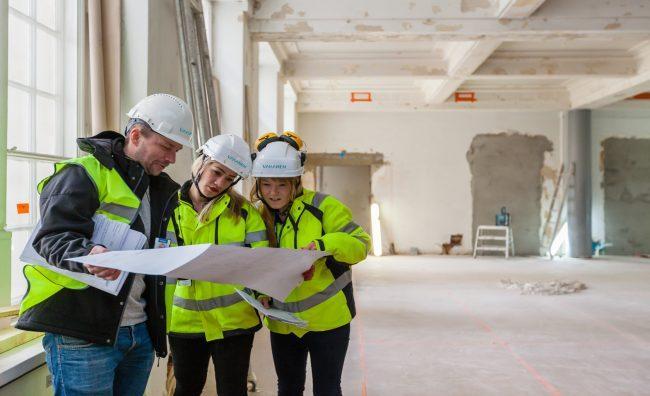 Tyntekijät tukimassa rakennuspiirustuksia