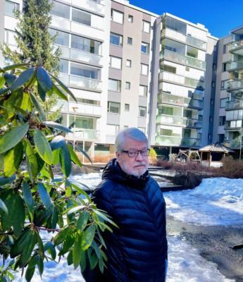 Asunto-osakeyhtiön pihalla otettu kuva, jossa näkyy kerrostalo ja asunto-osakeyhtiön hallituksen puheenjohtaja Matti Lehtonen.