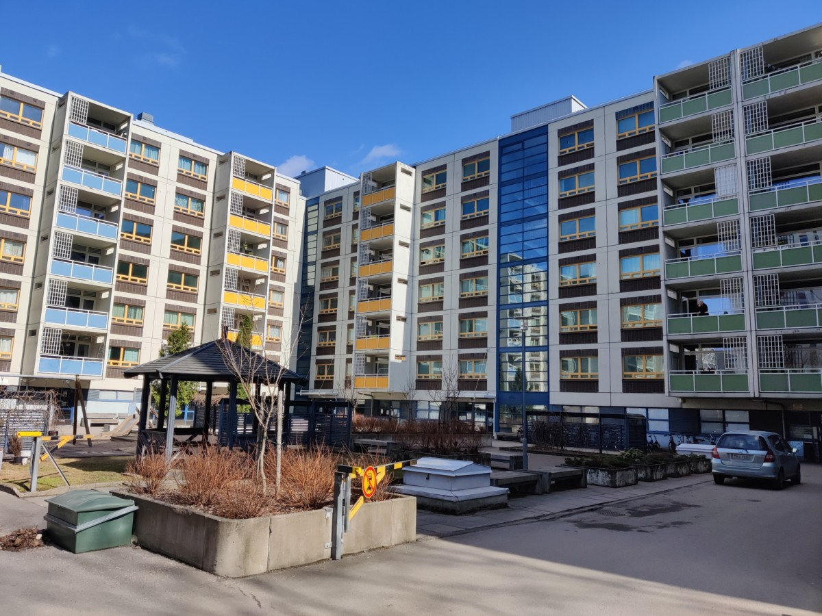 Asunto-osakeyhtiö Asemapäällikönkatu 2:n pihalla otettu kuva, jossa näkyy kerrostalo.