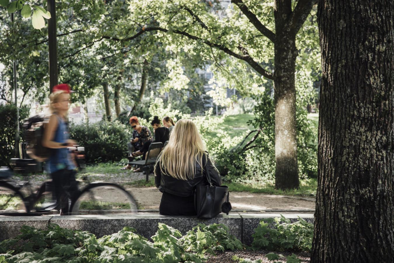 Nainen istuu puistossa Pasilassa. Kuva: Kuvatoimisto Kuvio Oy.