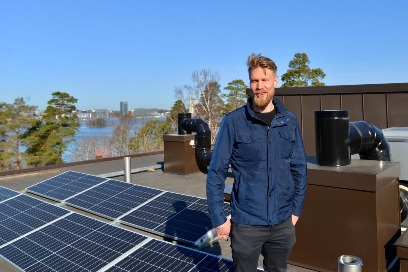 Katajaharjuntie 15:n hallituksen puheenjohtaja Vesa Tarvainen taloyhtiön katolla aurinkopaneeleiden edustalla.